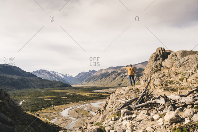 Male hiker looking at Patagonia Andes while standing on rock against sky- Argentina