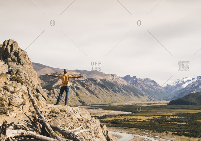 Male hiker with arms outstretched looking at Patagonia Andes while standing on rock- Argentina