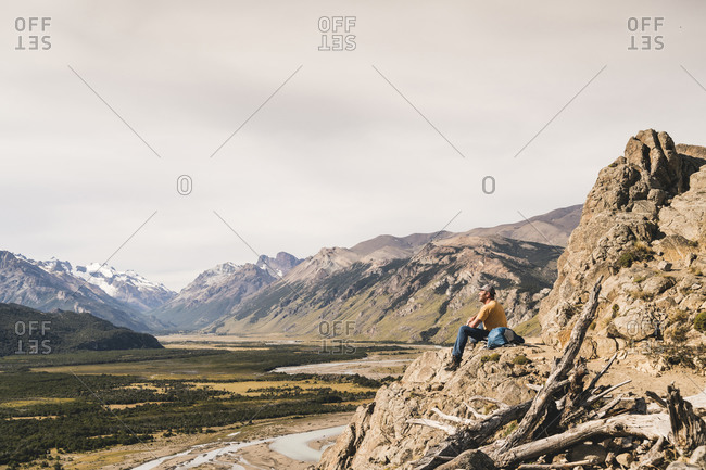 Male hiker sitting on rock against Patagonia Andes- Argentina