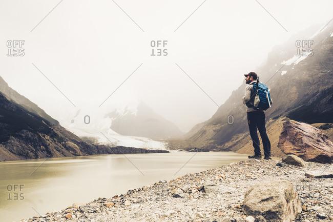 Mature man standing at lakeshore during foggy weather- Patagonia- Argentina