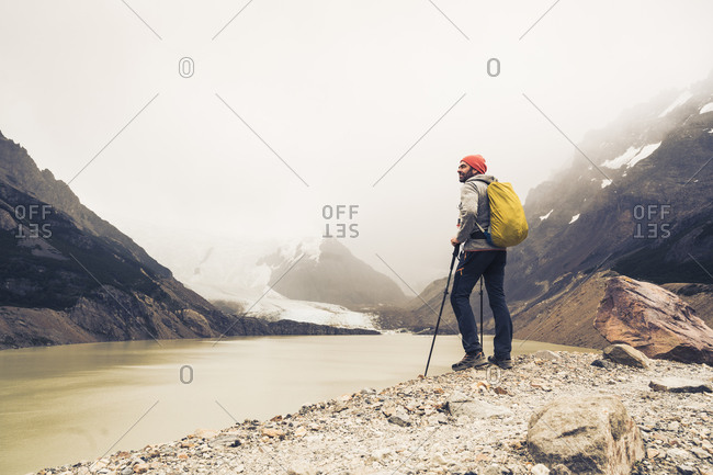 Man with hiking poles standing by lake against sky at Patagonia- Argentina