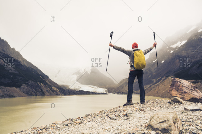 Man with arms outstretched holding hiking poles standing by lake at Patagonia- Argentina