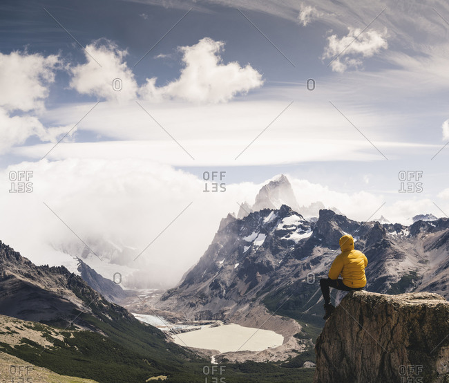 Man looking at snowcapped mountain while sitting on rock against sky- Patagonia- Argentina