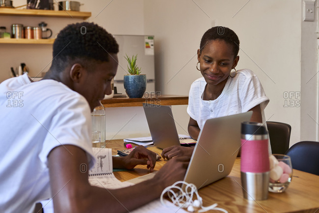 Young couple discussing doubts over laptop while studying at home