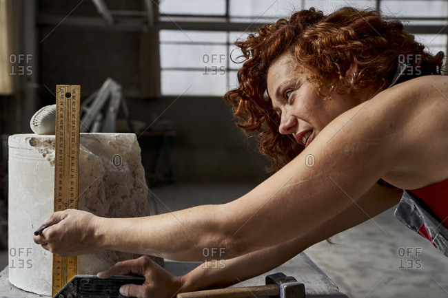 Close-up of woman measuring stone with ruler in studio