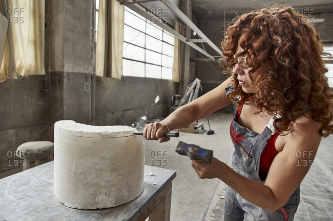 Female stonemason with curly hair carving stone on table in workshop