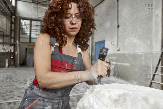 Close-up of woman with curly hair carving stone in workshop