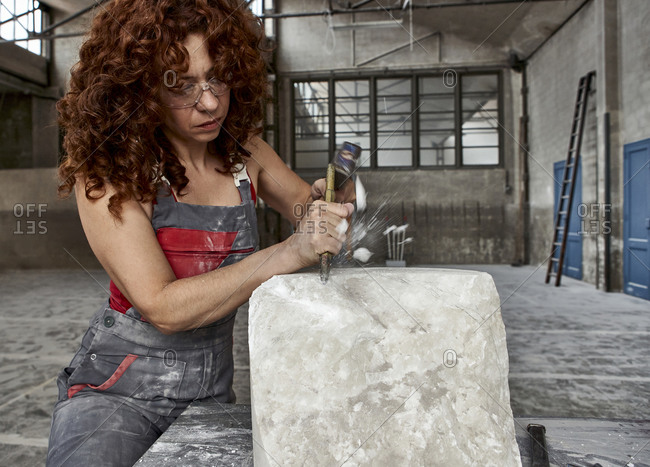 Female stonemason with curly hair carving stone in studio