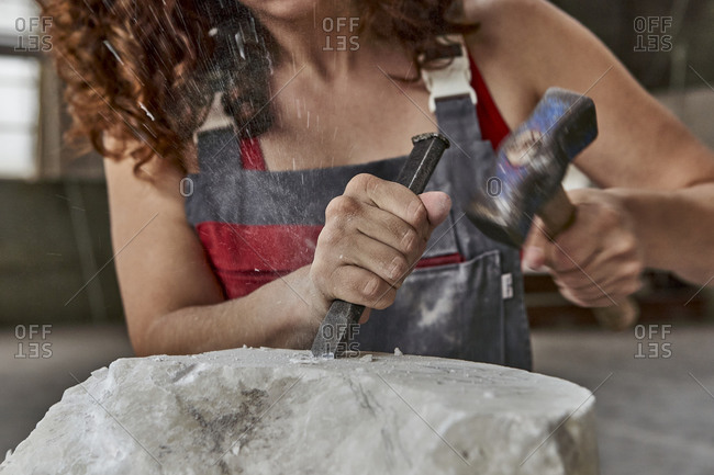 Close-up of female stonemason carving stone in workshop