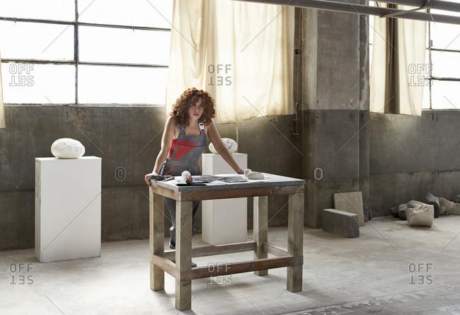 Female stonemason posing while standing by workbench in studio