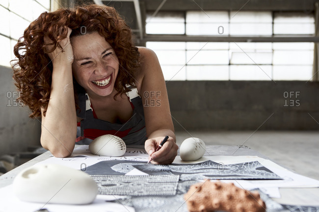 Close-up of cheerful woman drawing sketches on workbench in studio