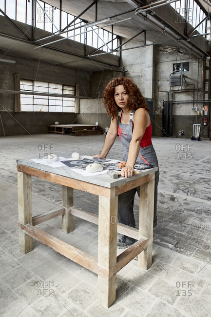 Confident female stonemason with sketches and work tools on table standing in studio