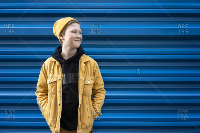 Thoughtful boy smiling while standing against blue shutter during sunny day