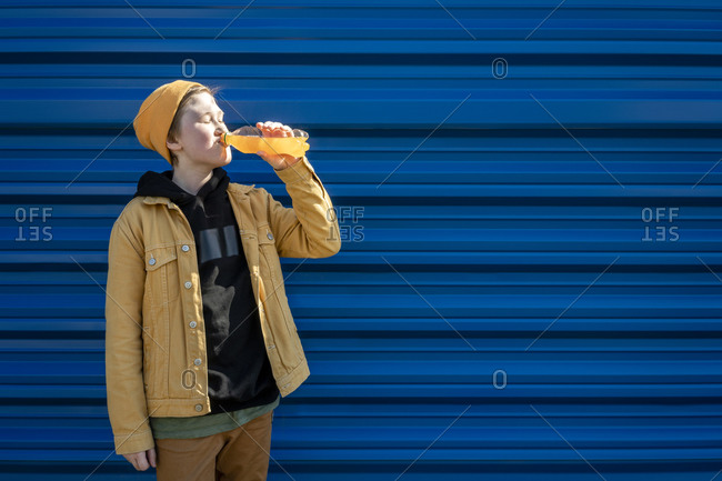 Boy drinking orange juice while standing against blue shutter during sunny day