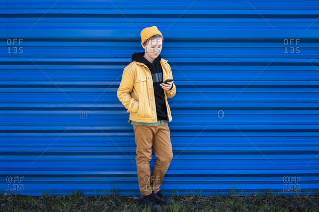 Boy using smart phone while standing against blue shutter