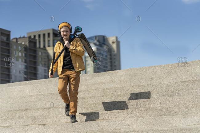 Boy carrying push scooter while moving down on steps against blue sky