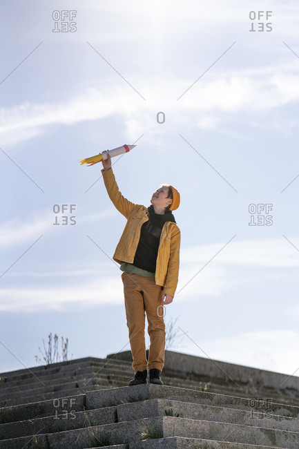Boy holding rocket toy while standing on steps against sky