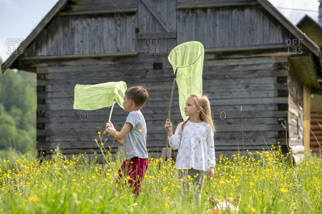 Friends catching butterflies with nets while standing amidst plants against cottage