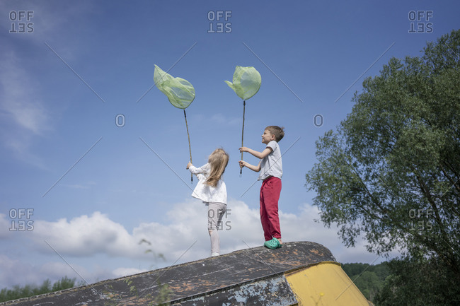 Friends catching butterflies with nets while standing on abandoned boat against blue sky