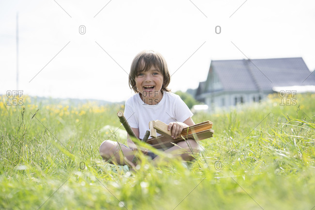 Cheerful cute boy holding model airplane while sitting on grassy land against clear sky
