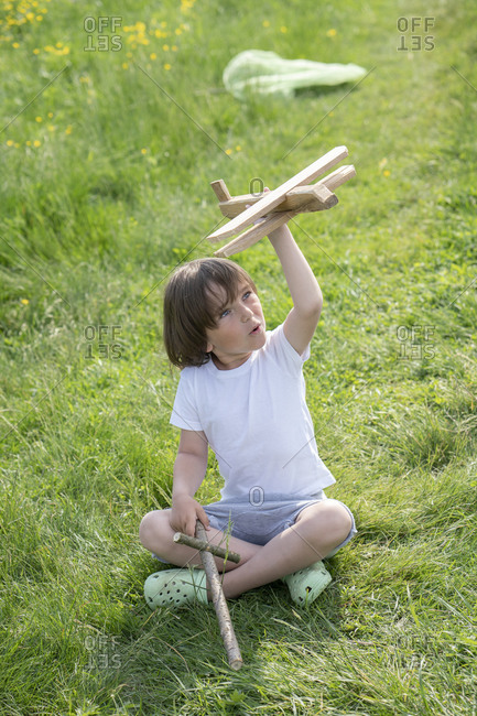 Playful boy flying model airplane while sitting on grassy land