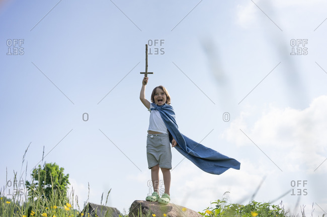 Boy wearing cape screaming while standing on rock against sky