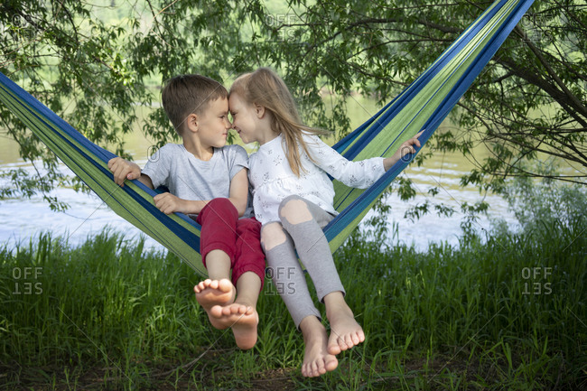 Cute friends with face to face sitting on hammock in forest