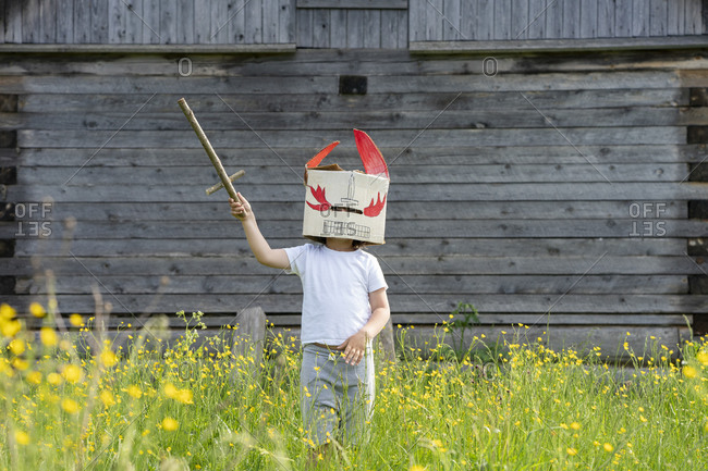 Boy wearing mask holding toy sword while standing amidst plants against cottage