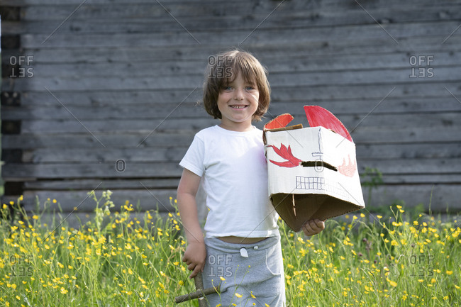Smiling boy holding mask and toy while standing amidst plants against cottage