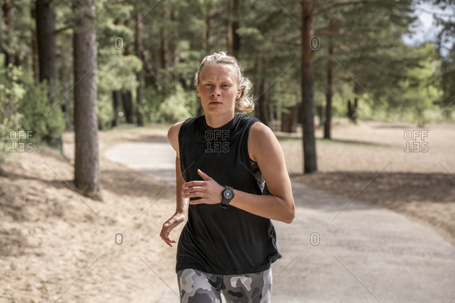 Young blond woman jogging in the woods