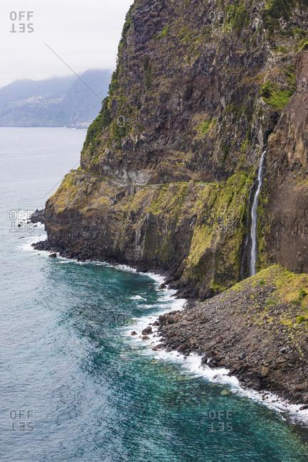 Portugal- Porto Moniz- Veu da Noiva waterfall splashing down coastal cliff of Madeira Island