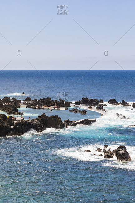 Portugal- Porto Moniz- Small rocky bay along shore of Madeira Island with clear line of horizon over Atlentic Ocean in background