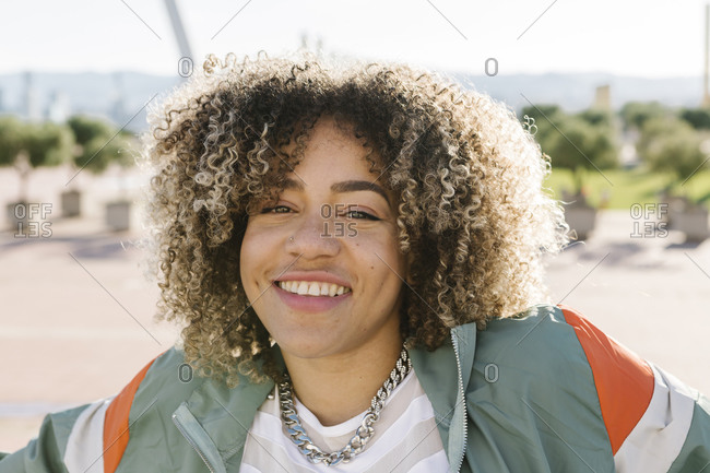 Happy young woman with curly highlighted hair during sunny day