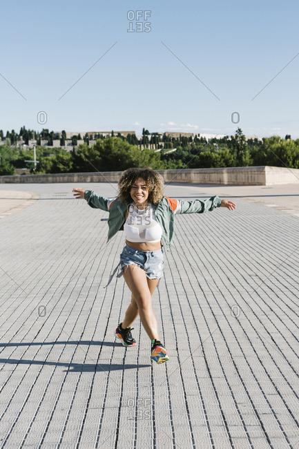 Cheerful fashionable woman dancing on city street during sunny day