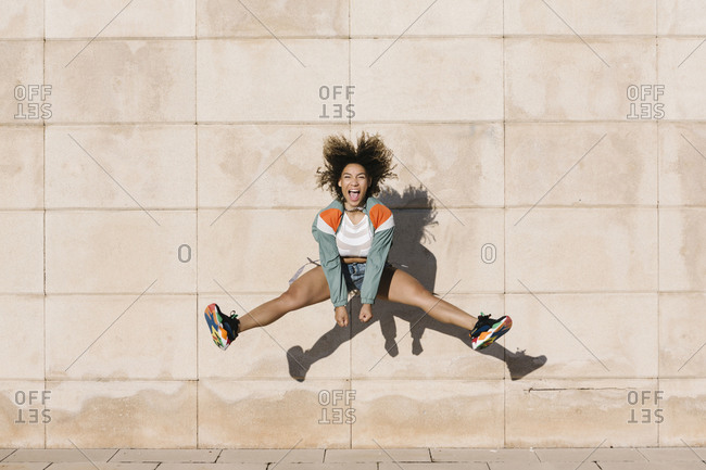 Excited young woman screaming while jumping against wall during sunny day