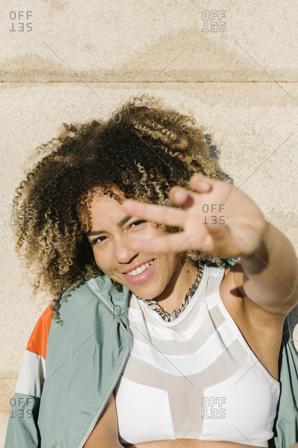 Happy young woman gesturing peace sign during sunny day