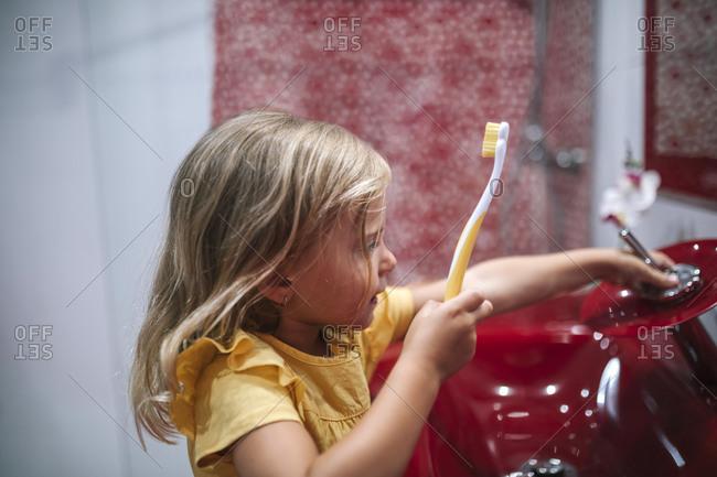 Little girl brushes her teeth in the bathroom
