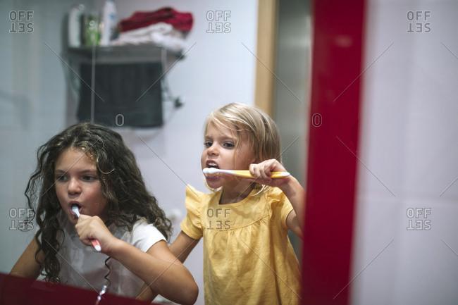Sisters brushing their teeth in front of the bathroom mirror