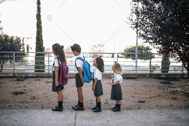 Four children lined up with backpacks at school