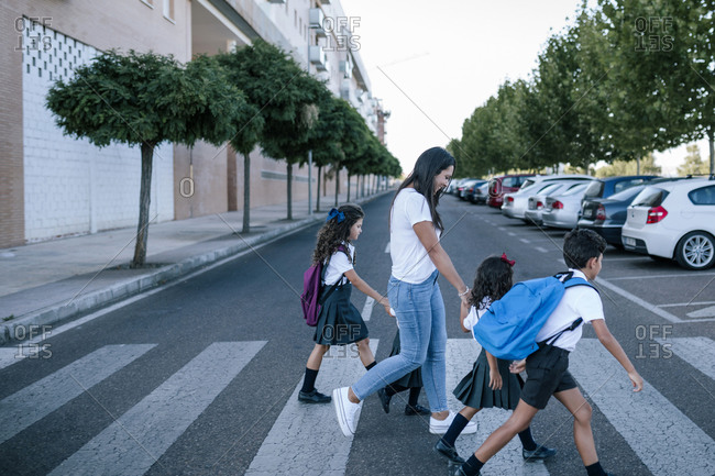 Young woman with group of four school children crossing a zebra crossing