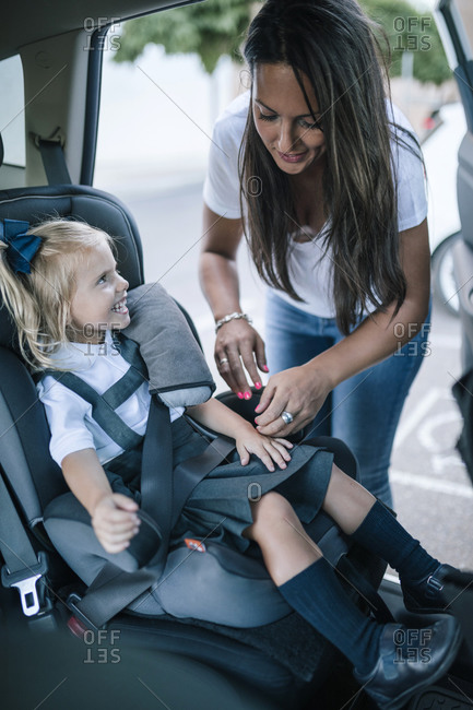 Young woman putting the seat belt on her daughter in the car to go to school