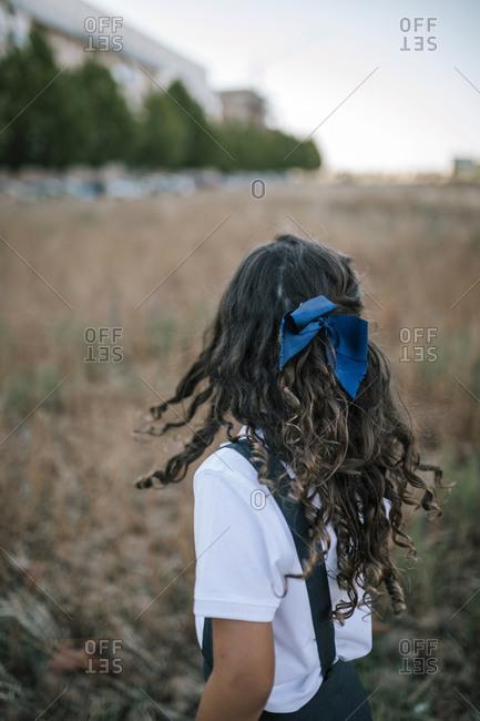Portrait of little girl shaking curly hair in school uniform in field