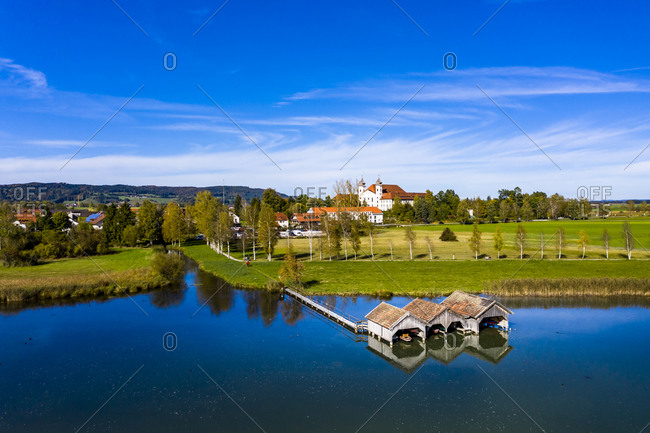 Germany- Bavaria- Schlehdorf- Helicopter view of lakeshore boathouses in summer