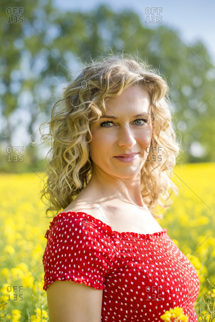 Close-up of beautiful woman wearing red dress standing against oilseed rapes