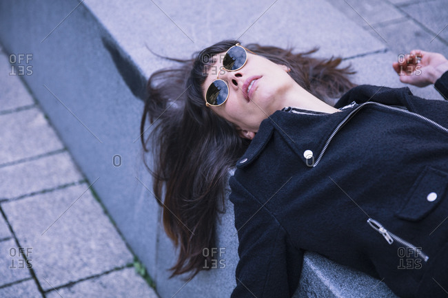 Middle aged businesswoman with sunglasses- lying on concrete bench