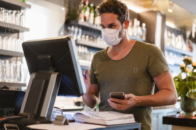 Restaurant manager with protective mask using computer and smartphone
