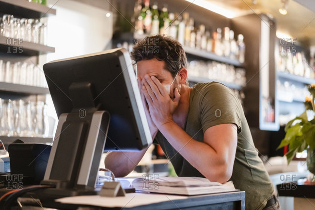 Restaurant manager with hands in face during corona crisis