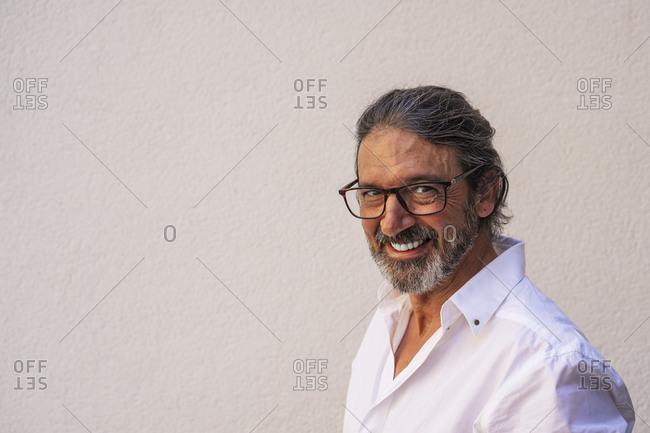 Happy mature man wearing eyeglasses against gray wall