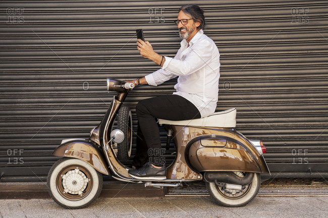 Happy mature man taking selfie while sitting on motor scooter against black shutter