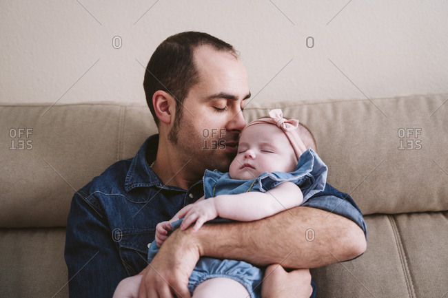 Father carrying sleeping baby girl on sofa at home